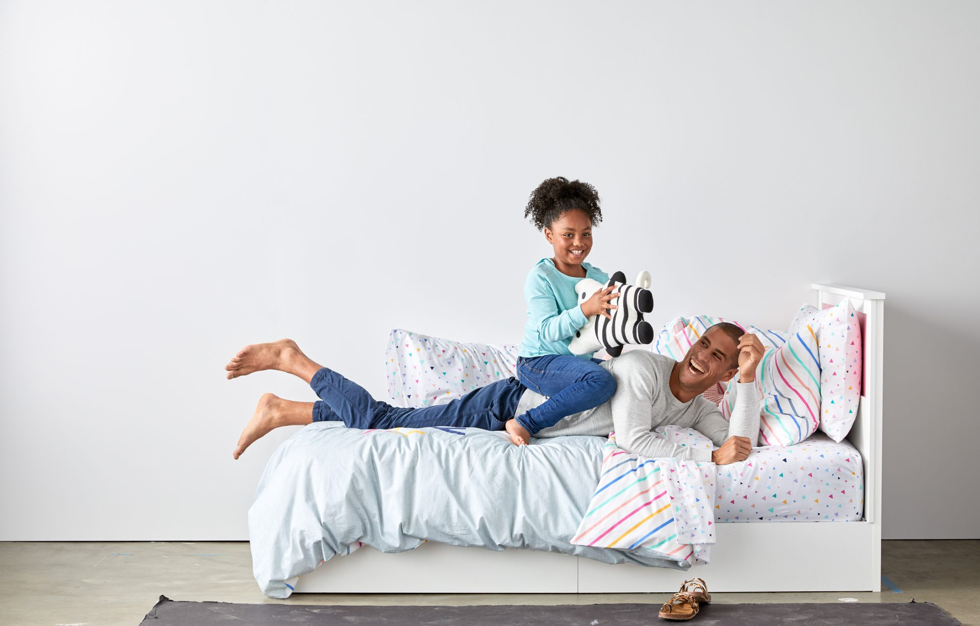 dad and daughter playing on bed